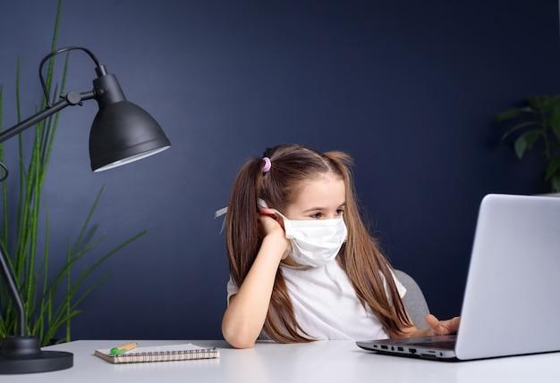Дистанционное обучение онлайн-образование. школьница в медицинской маске учиться на дому, работать на ноутбуке ноутбука и делать домашнее задание в школе. концепция карантинного коронавируса