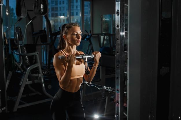 ブロックシミュレーターで推力。上腕二頭筋の拡張。ジムで運動女性のトレーニング。