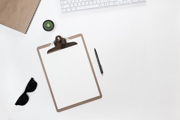 Рабочий стол современного белого блоггера с белой клавиатурой, папкой-планшетом, солнцезащитными очками и кактусом