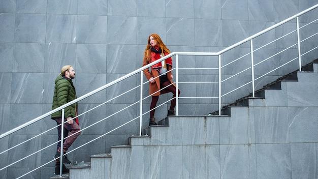 Модная девушка и парень поднимаются по улице по лестнице