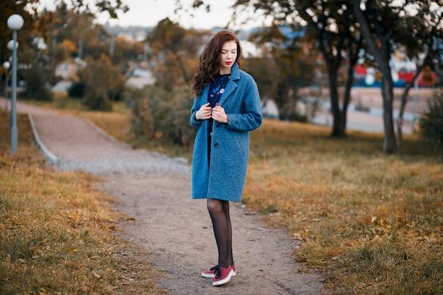 Модная молодая кудрявая женщина осенью в парке в синем пальто и красных кроссовках