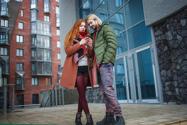 近代的な都市で一緒に立っている若いカップル