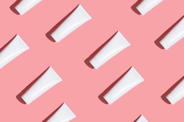 Бесшовные шаблон белые кремовые трубки на светло-розовом столе. уход за кожей лица, рук, ног и тела.