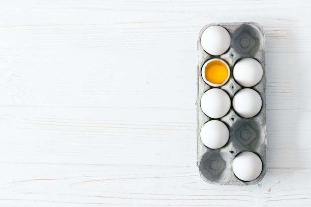 白い木製の背景に卵を梱包します。卵黄と壊れた卵。