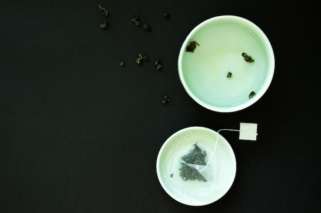 Японская чашка чая и блюдце с пакетиком чая листья на черном фоне. чайная вечеринка.