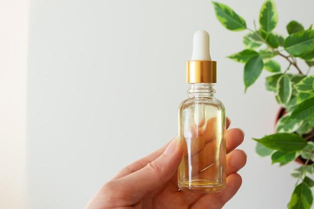 Рука женщины держа суть сыворотки в стеклянной бутылке и листья на белой стене. косметический продукт для ухода за кожей. увлажняющий крем для лица. концепция натуральной и органической косметики, копия пространства