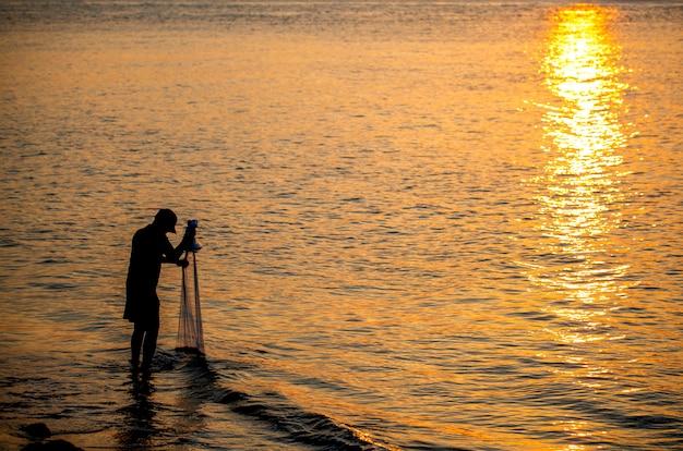Рыбак забрасывает сеть морем утром, на рассвете