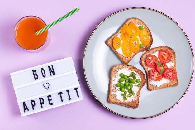 野菜のサンドイッチとにんじんジュースとクリームチーズのプレートで紫色の表面にボン食欲レタリング