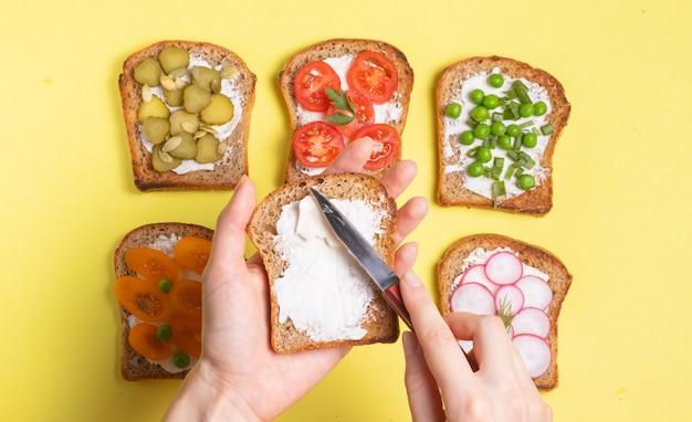 野菜ベジタリアンのフィリングの朝食サンドイッチ女性はクリームチーズトーストを広める