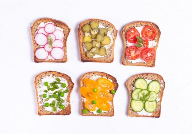 白い表面に野菜ベジタリアンのトッピングの朝食サンドイッチ