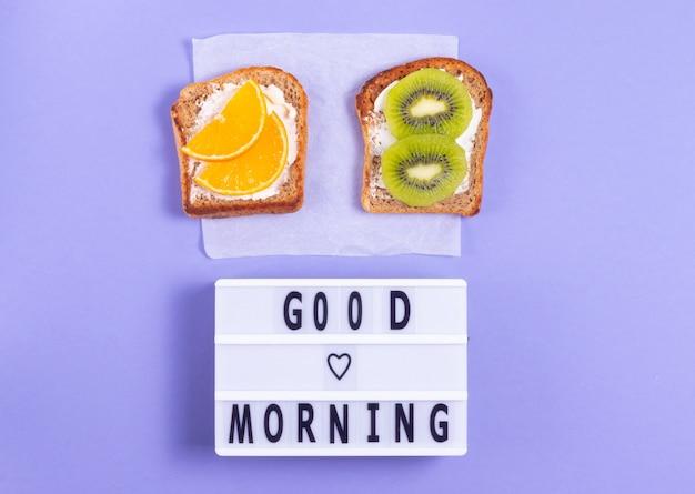 Доброе утро надписи с фруктовыми бутербродами на завтрак на фиолетовой поверхности