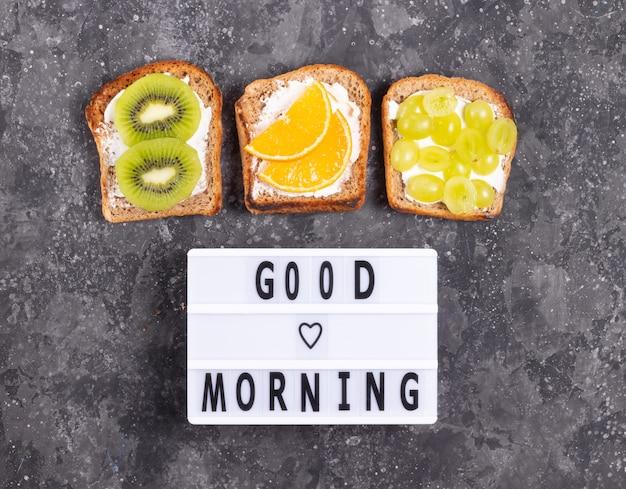 Надпись доброе утро с фруктовыми бутербродами со сливочным сыром на серой поверхности
