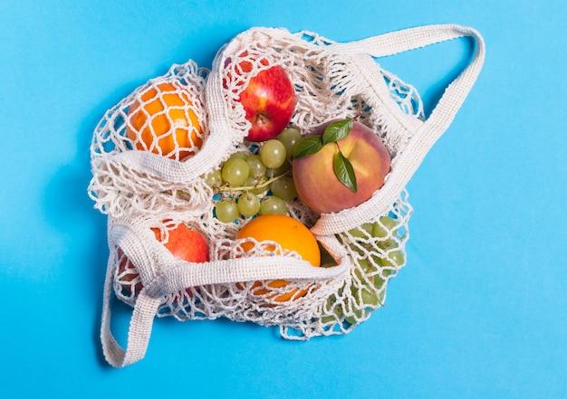 オレンジ色の表面にストリングバッグに入ったオレンジ、リンゴ、ピーチ、ブドウ