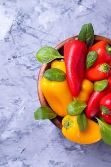 Красные и желтые маленькие болгарские перцы в деревянной тарелке на серой поверхности