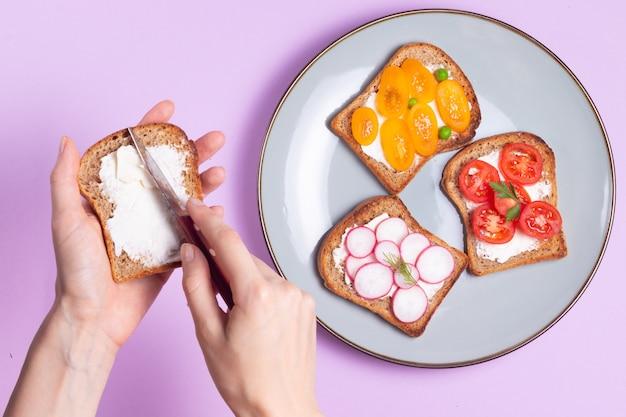 野菜と紫の表面にクリームチーズのベジタリアンサンドイッチを準備する女性