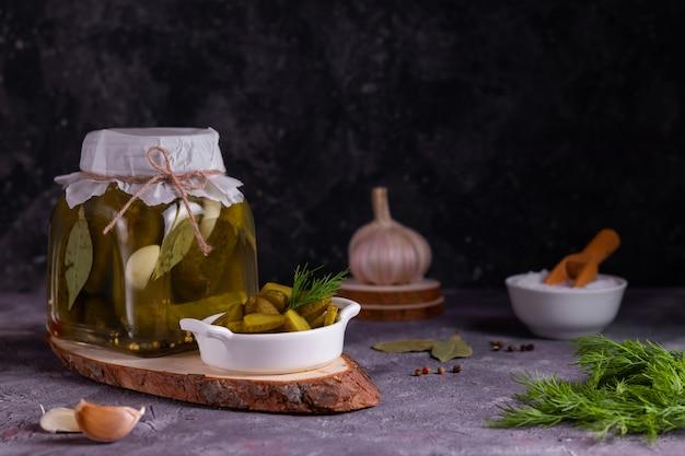 ベイリーフ、ニンニク、ディルを灰色の表面上のガラスの瓶で発酵させたキュウリの缶詰の調理プロセス