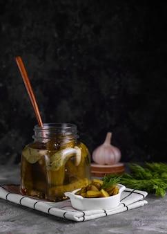 暗い壁にスライスしたキュウリと白い皿が付いているガラスの瓶にベイリーフ、ニンニク、ディルと発酵させたキュウリの缶詰