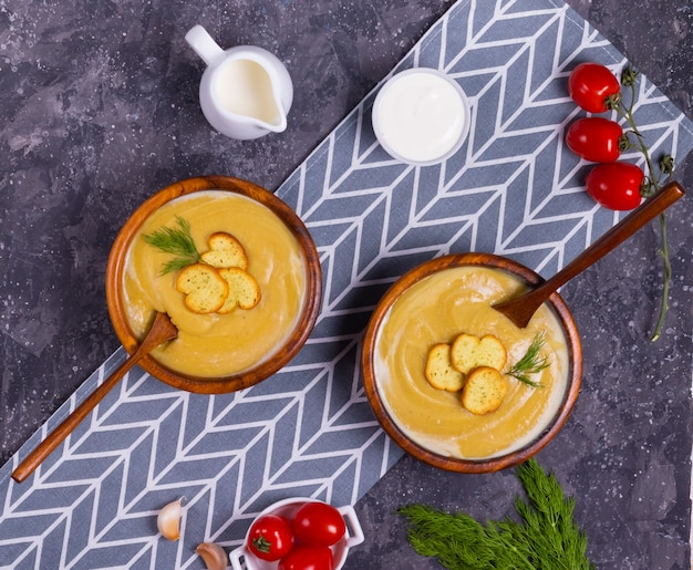 Крем-суп из чечевицы и тыквы с укропом в деревянных тарелках с деревянными ложками с помидорами черри на серой салфетке