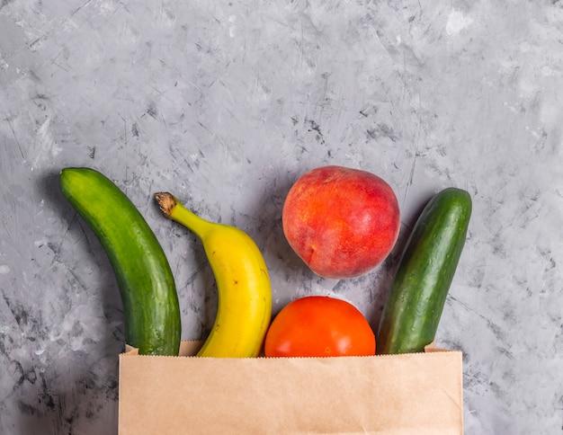 紙袋に入った新鮮な果物と野菜