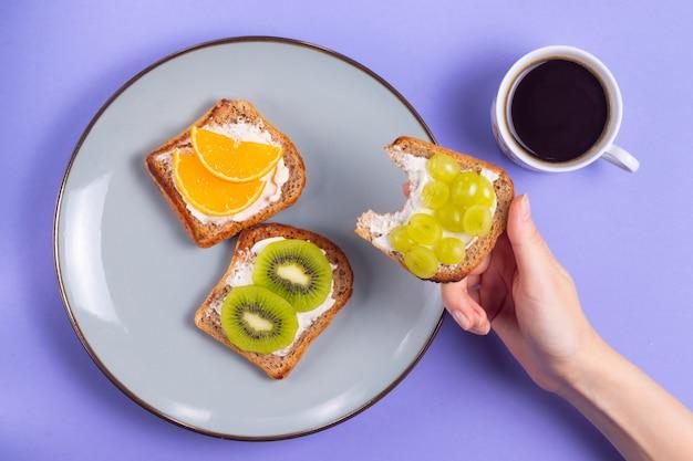 コーヒーとプレートにフルーツとクリームチーズのサンドイッチ