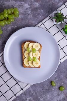 Хрустящие тосты с бананом и виноградом на сером фоне здорового питания
