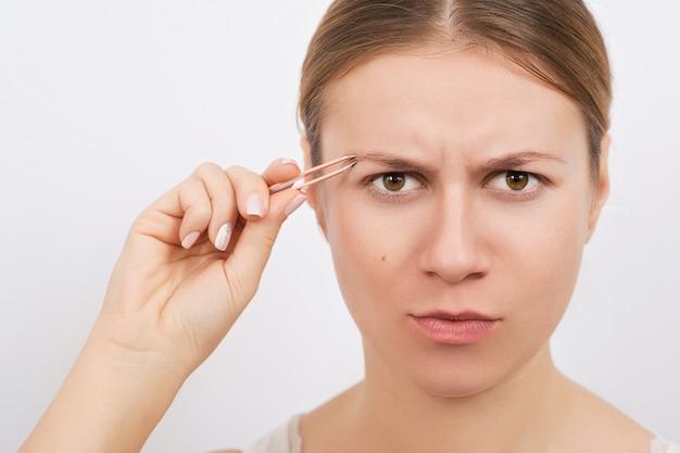 Женщина выщипывает брови пинцетом