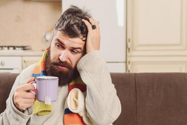 Больной человек, сидя на кровати у себя дома. бородатый мужчина чувствует себя холодно, держит теплый и горячий чай. больная концепция лихорадки молодого человека. лечебный чай зимой. заболел бородатый парень, страдающий от простуды. больной кобель с головной болью.