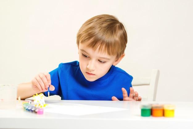 美術の授業で陶器の模型を描く子供。美術学校。創造的な教育と開発。幼稚園で絵を描く子。彼の絵を楽しんでいるかわいい男の子。
