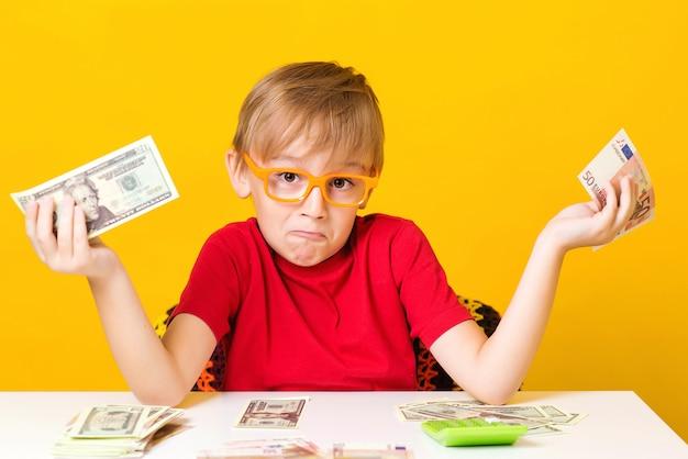 お金を保持していると新しいビジネスを考えて小さな男の子が起動します。黄色の背景の上の現金で眼鏡の小さな教授