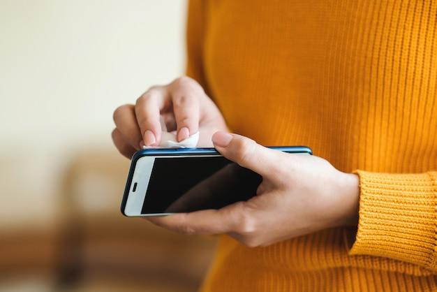 コロナウイルス予防のための防腐性ウェットワイプで電話を消毒する女性。