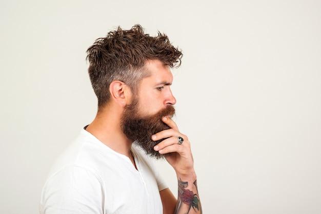 白い背景の上のスマートで創造的なハンサムな男のプロフィール。ひげを生やした男は、問題を解決しようと考えています。厳しい決断を下すヒップスター