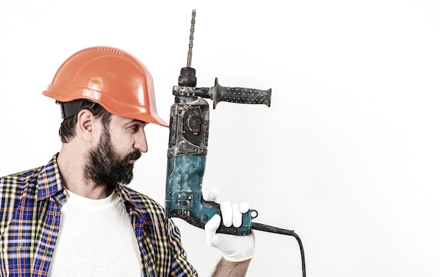 Бородатый строитель работник с дрелью. рабочий в оранжевом шлеме. профессиональные инструменты.