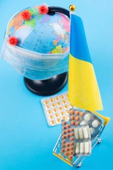 ウクライナの旗。薬と一緒に買い物カゴ。フェイスマスクのグローブ。ヘルスケアの問題。ウクライナでコロナウイルスと戦う。コロナウイルス検疫。