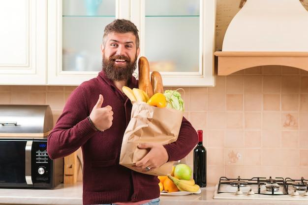 食物と一緒に紙袋を保持している幸せなひげを生やした男。モダンなキッチンで食料品の袋を持つ男。食品、家庭への製品の配達。