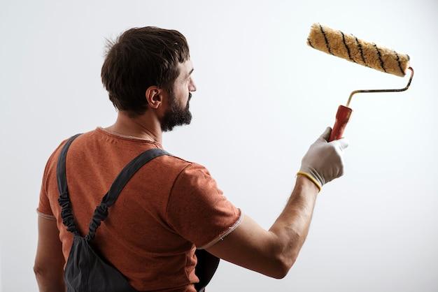 Маляр работает. концепция ремонта дома. умелый и профессиональный художник. кисть валиковая малярная.