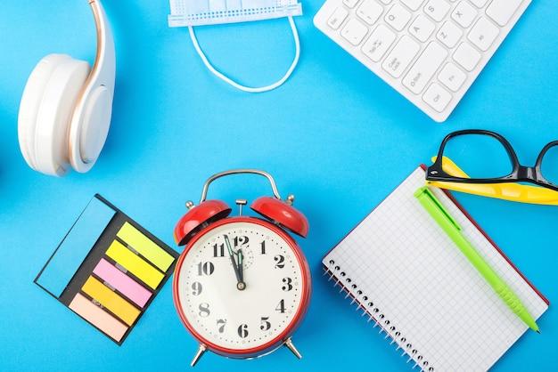 ヘッドフォン、ラップトップ、空白のノートブック、医療マスク、時計のあるワークスペース。遠隔教育や仕事の時間です。