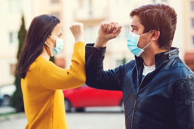 屋外の肘と若いカップルの挨拶。コロナウイルスを防ぐための新しいスタイルで一緒に挨拶する男女。コロナウイルスエピデミック。