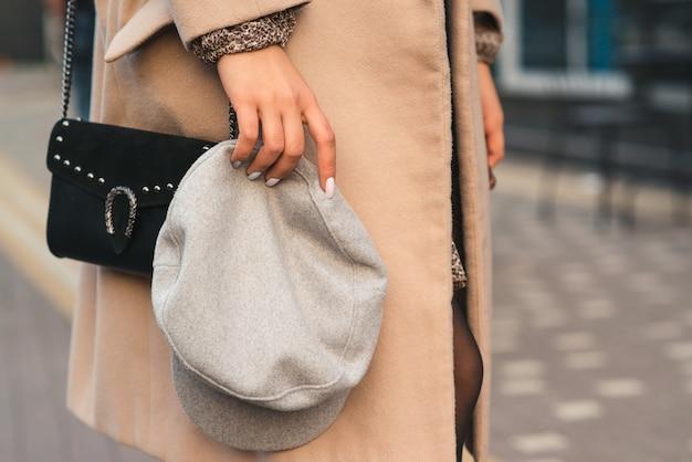 Женщина, держащая шапку, крупным планом. молодая женщина с черной сумочкой. весенняя и осенняя мода. серая модная шапка. женская мода.