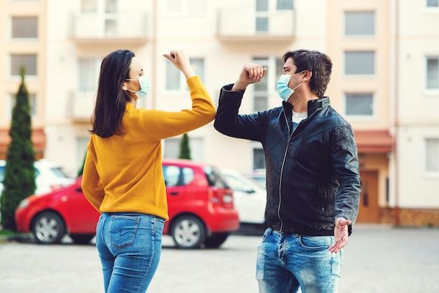 コロナウイルスエピデミック。肘で挨拶する男と女。コロナウイルス検疫。世界のグローバルなパンデミック。屋外で肘を振る友人。