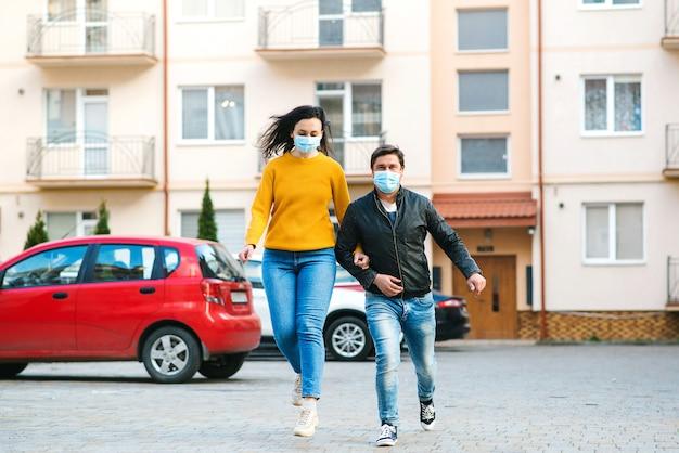 家の外の医療マスクの家族。コロナウイルス検疫。人々は公共の場所でフェイスマスクを着用する必要があります。世界のグローバルなパンデミック。