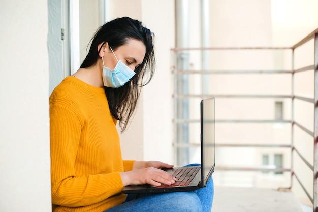女性変顔マスク。バルコニーのラップトップに取り組んでいる女の子。テクノロジー、レジャー、ライフスタイル。フリーランサー、リモートワーク。