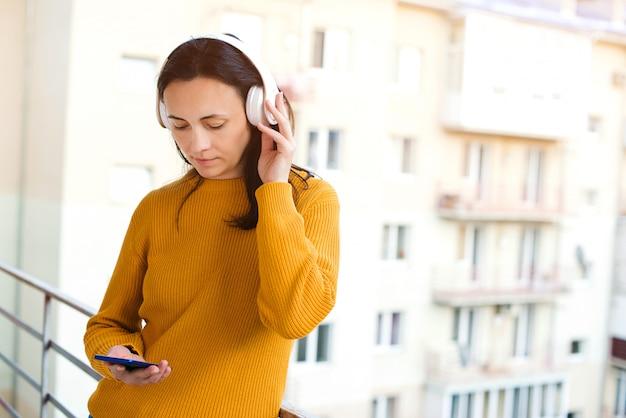 バルコニーで新鮮な空気を呼吸のヘッドフォンを持つ若い女性。携帯電話とワイヤレスヘッドフォンを使用しての女性。在宅でのコンセプト。