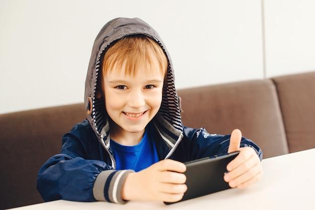 幸せな少年が携帯電話でゲームをプレイします。外のテラスでスマートフォンで動画を見て子供。