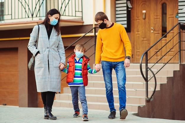 コロナウイルス検疫。散歩に行く家族。両親と子供が屋外でサージカルマスクを着用しています。