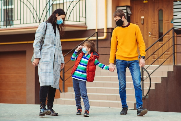 予防コロナウイルス。屋外保護マスクを身に着けている若い家族。コロナウイルス検疫。