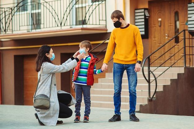 母は息子にフェイスマスクをつけます。散歩に行く家族。サージカルマスクを身に着けている親と子供。コロナウイルスの拡散を止めます。