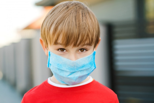 Маска для лица для защиты от вспышки коронавируса. ребенок носить маску медицины на открытом воздухе. коронавирус эпидемия.