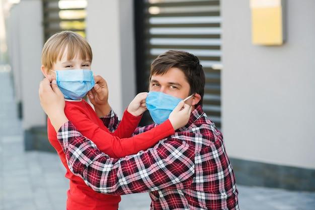 父は息子のフェイスマスクを屋外に置きます。コロナウイルスの流行、ウイルスの症状。検疫中の保護のためにマスクを着用している家族。