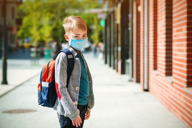 Школьник носить маску во время эпидемии. обратно в школу концепции. милый мальчик снаружи в школе имея полезного время работы.