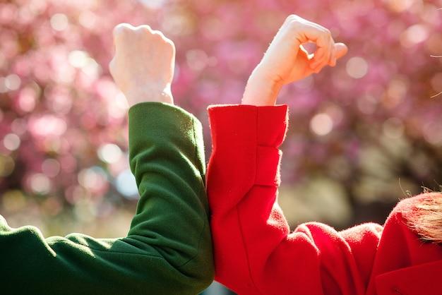 屋外の肘で挨拶する女性。社会的距離の概念。春の公園でひじをぶつけている二人の女の子。